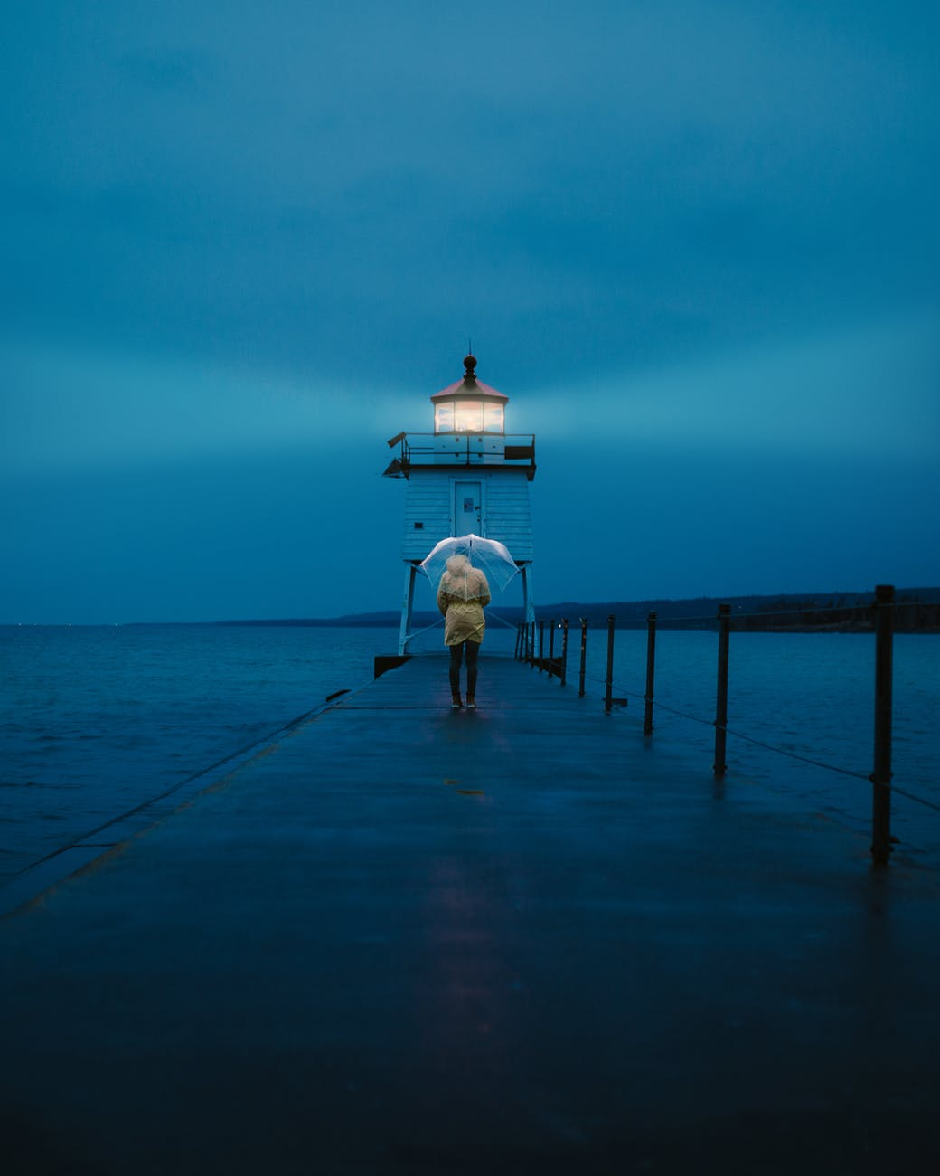 photo of a person standing on footbridge leading to a lighthouse